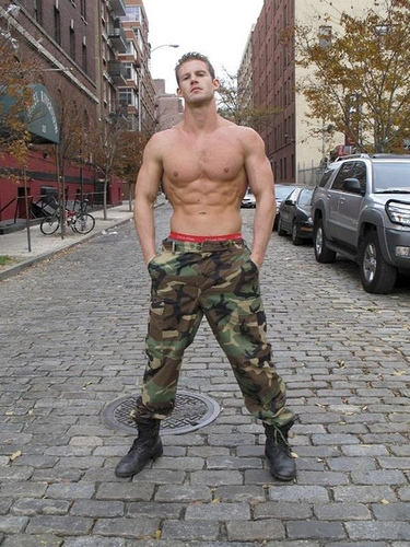Hunky guy in camo trousers and boots